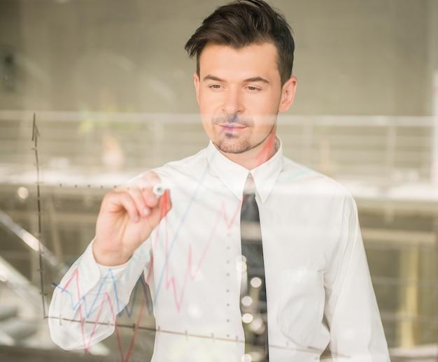 De mens kleedde formele tekenings bedrijfsstrategie op venster.