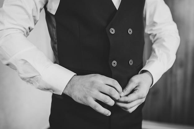 De mens knoopt zijn vest dicht. detailopname. perfect tot in het kleinste detail. moderne zakenman.