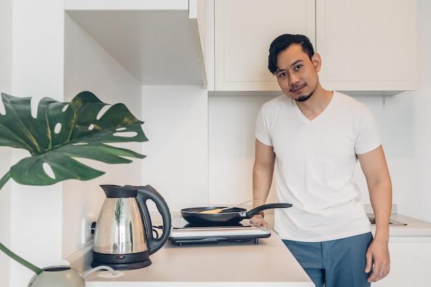 De mens kookt het ontbijt in de keuken.