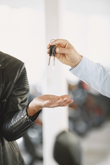 De mens koos voor motorfietsen in de moto-winkel. man in een zwart jasje. manager met klant.