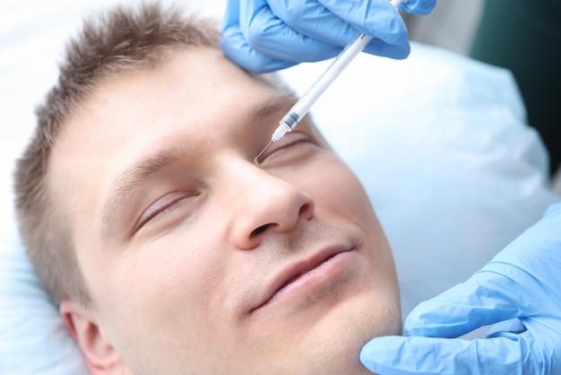 De mens krijgt een verjongende injectie in zijn gezicht