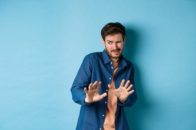 De mens krimpt ineen en blijft weg van iets smerigs, kijkt opzij en strekt zijn handen uit om slechte deal af te wijzen, staande op een blauwe achtergrond.