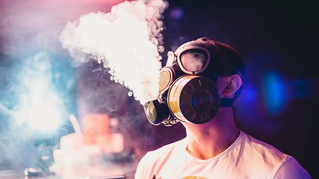De mens laat wolken van waterpijp roken in een gasmasker