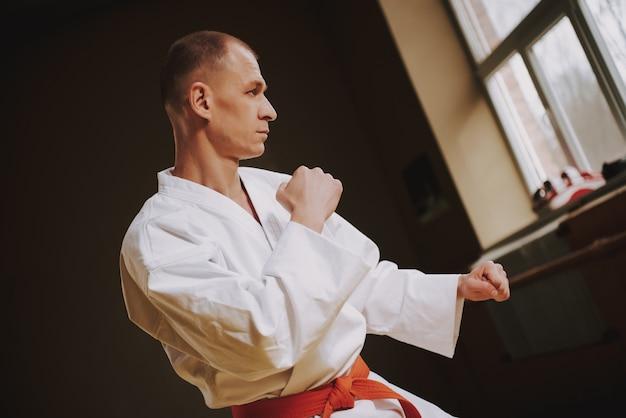 De mens leert technieken van kung fu-stakingen in de hal.