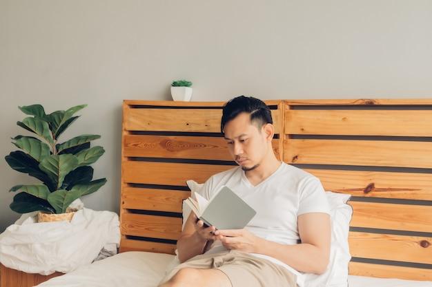 De mens leest laat in de middag een boek op zijn bed.