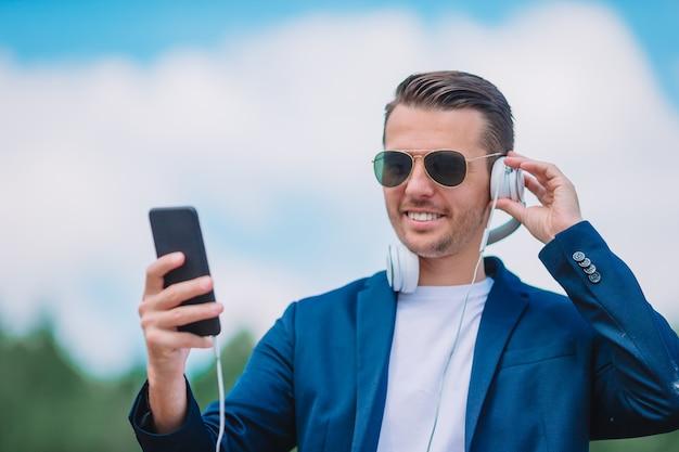 De mens leest tekstbericht op mobiele telefoon tijdens het wandelen in het park