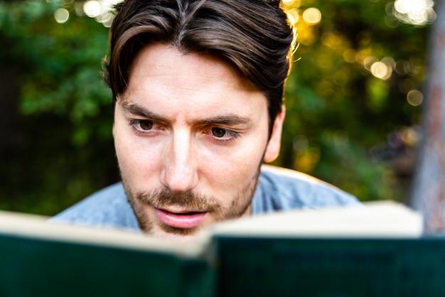 De mens leest verbaasd over een oud boek over avonturen, verbeelding en literatuur.
