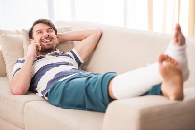 De mens ligt op bank met gebroken been en spreekt telefonisch.