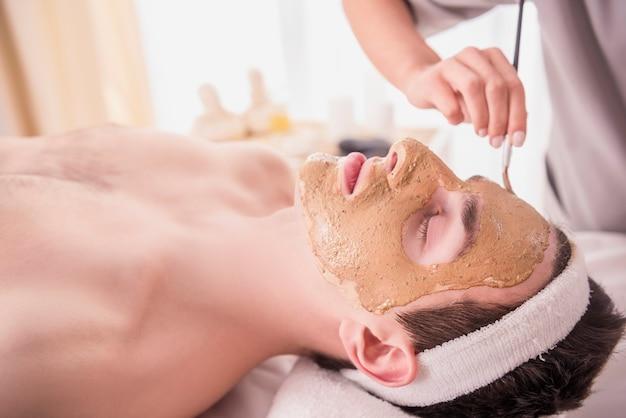 De mens ligt op het bed en ze zetten een masker op zijn gezicht.