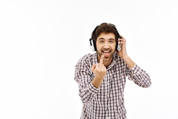 De mens luistert muziekhoofdtelefoons, toont middelvinger