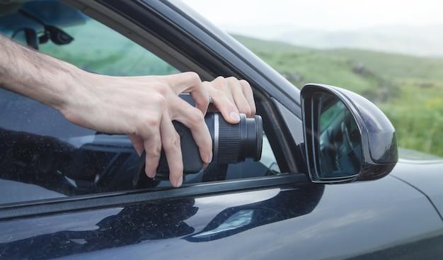 De mens maakt foto's in de autospiegel.