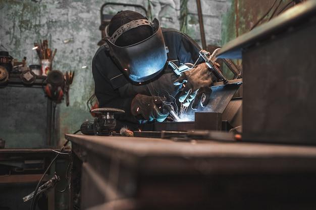 De mens maakt ijzerproducten.