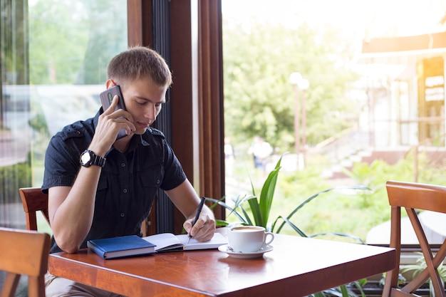 De mens maakt nota's in notitieboekje en het spreken op de telefoon in koffiewinkel