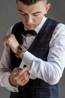 De mens maakt zich klaar voor het werk door zijn zakelijke shirt dicht te knopen. de ochtendvoorbereiding van de bruidegom vóór huwelijk