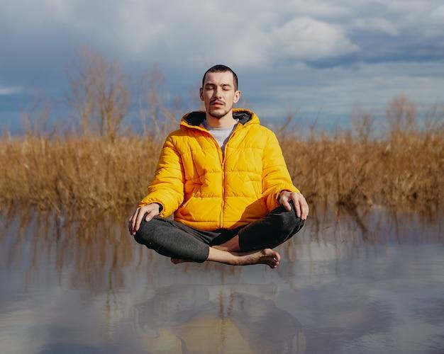 De mens mediteert bij het water