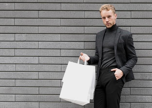 De mens met dient zijn zak in kijkend aan de camera