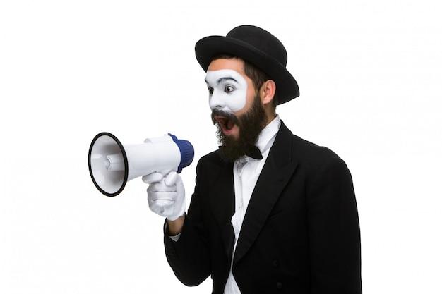 De mens met een gezicht bootst schreeuwend in megafoon na