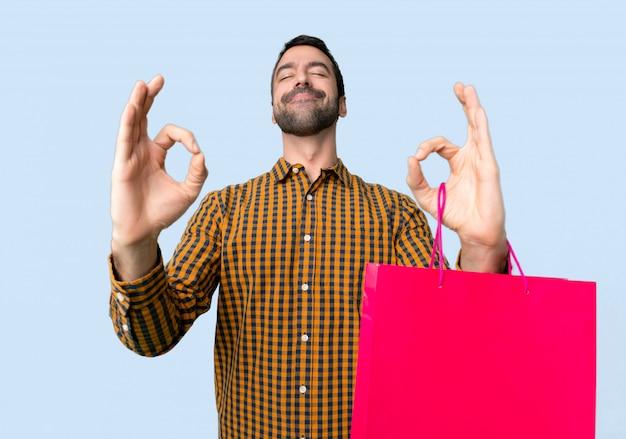 De mens met het winkelen zakken in zen stelt op geïsoleerde blauwe achtergrond