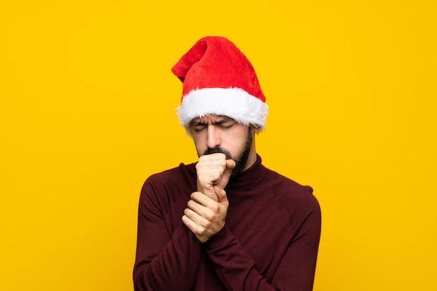 De mens met kerstmishoed over geïsoleerde gele muur lijdt aan hoest en voelt slecht