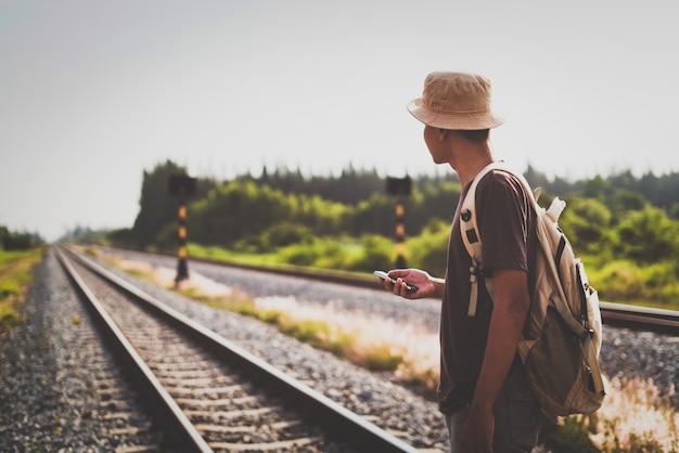 De mens met rugzak die op spoorweg weggaan en benadrukt aan geduld en onderzoek probeert stap vooruit naar doel.