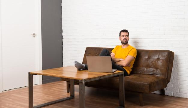 De mens met zijn laptop in een ruimte met verwart gezichtsuitdrukking terwijl bijt lip