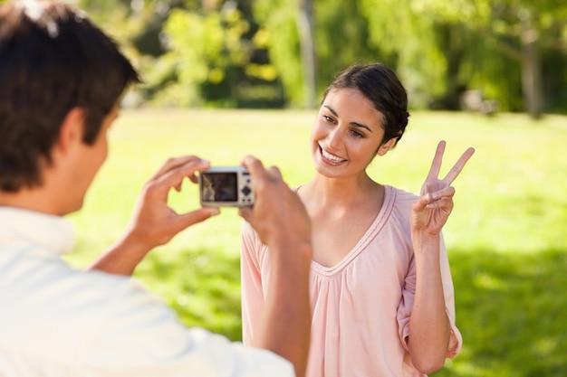 De mens neemt een foto van zijn vriend die het vredesteken geeft