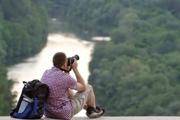 De mens neemt foto's van een heuvel in het oppervlak van bos en rivier