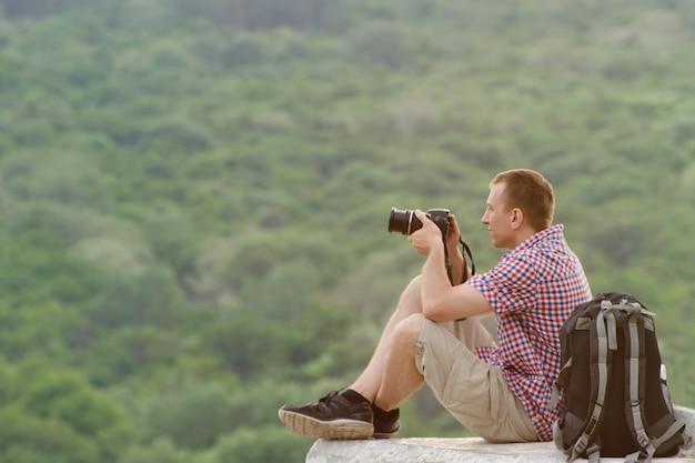 De mens neemt foto's van een heuvel in het oppervlak van het bos