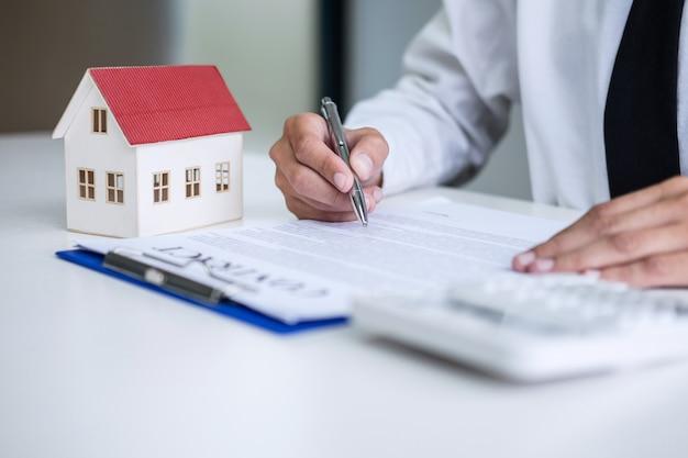 De mens ondertekent een huisverzekeringspolis op huislening, zakenman die contractverzekering ondertekenen