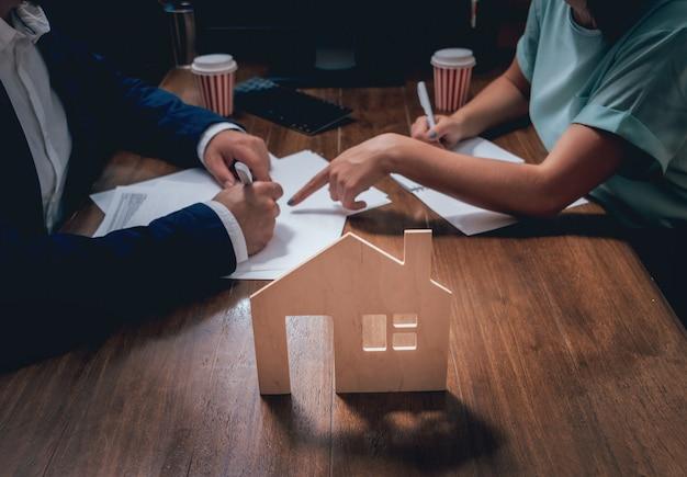 De mens ondertekent een huisverzekeringspolis op huisleningen. makelaar met klant voor contractondertekening.