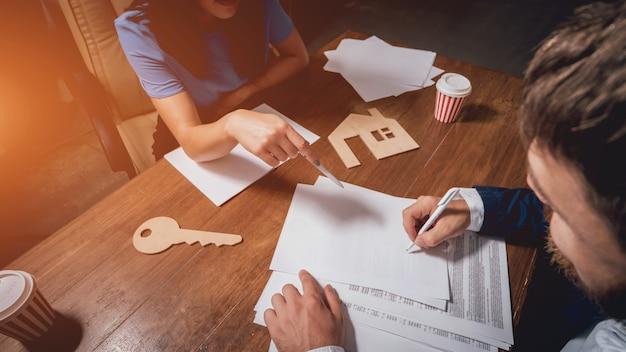 De mens ondertekent een huisverzekeringspolis op huisleningen. makelaar met klant
