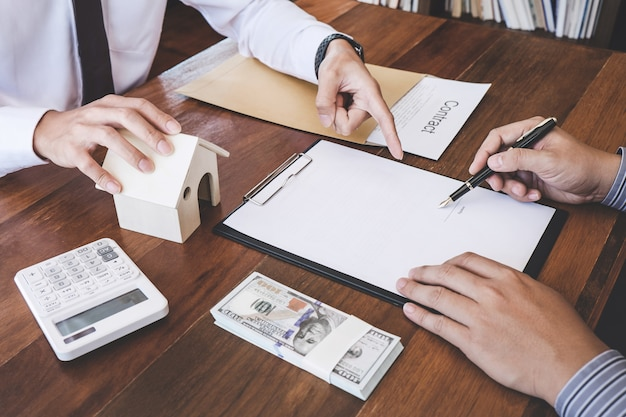 De mens ondertekent een huisverzekeringspolis op huisleningen, verzekeringsagent die investering analyseren