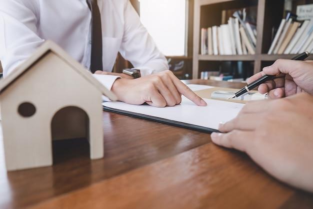 De mens ondertekent een huisverzekeringspolis op huisleningen, verzekeringsagent die over de lening van de huisinvestering analyseren