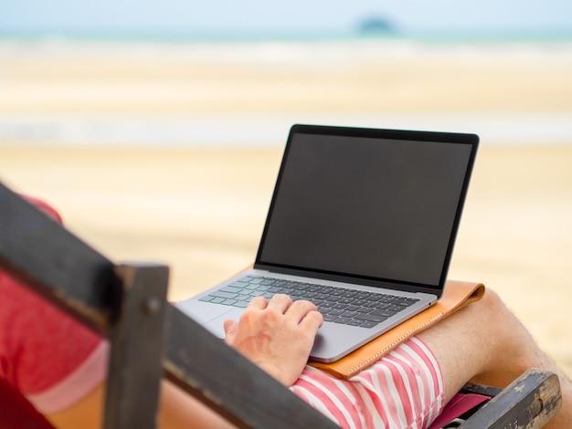 De mens ontspant op kampbed en online het werken terwijl op vakantie bij het strand in thailand