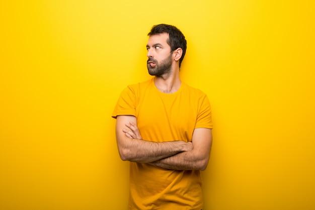 De mens op geïsoleerde trillende gele kleur met verwart gezichtsuitdrukking terwijl bijtlip