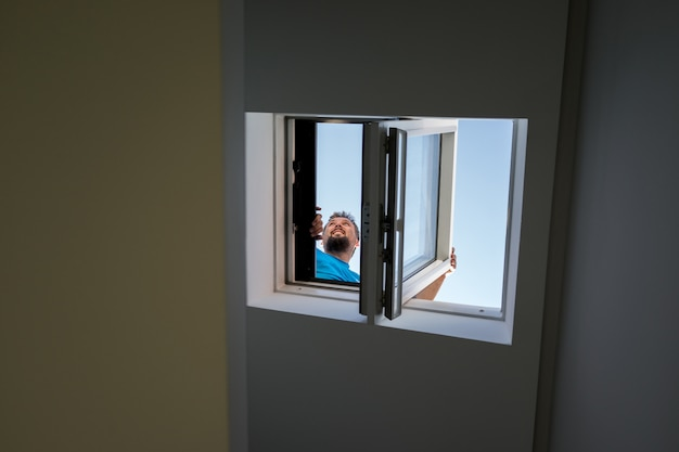 De mens op het dakvenster bekijkt binnen