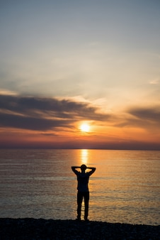 De mens op het strand waardeert mooie zonsopgang met zijn handen omhoog