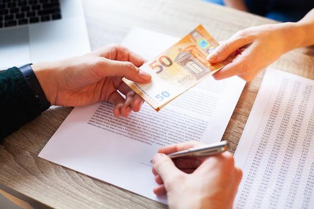 De mens op kantoor ontvangt de steekpenningen voor het ondertekenen van het contract.