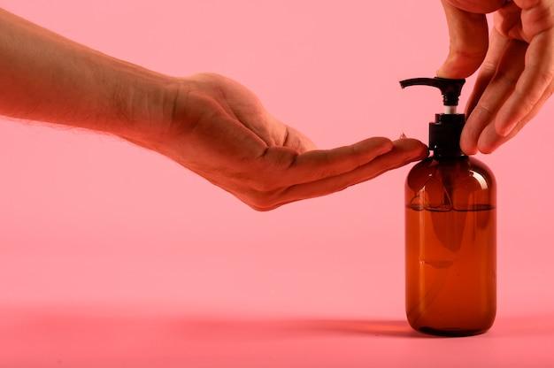 De mens overhandigt duwende pomp plastic fles die op roze achtergrond wordt geïsoleerd