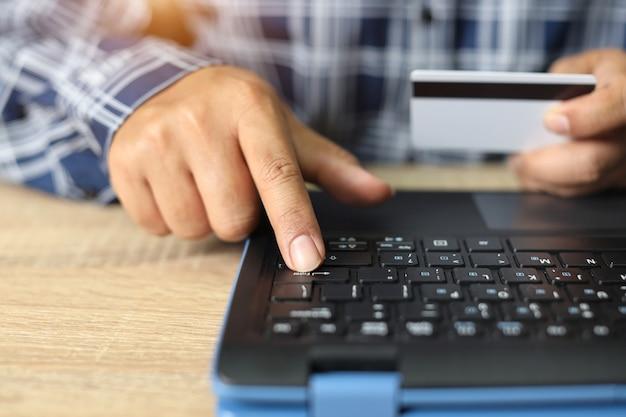 De mens overhandigt het winkelen en online betaling door laptop met creditcard te gebruiken