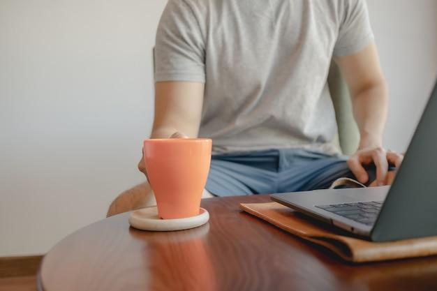 De mens pakt een oranje koffiekop terwijl hij op zijn laptop werkt.
