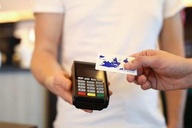 De mens past kaart op terminal toe en verricht betaling