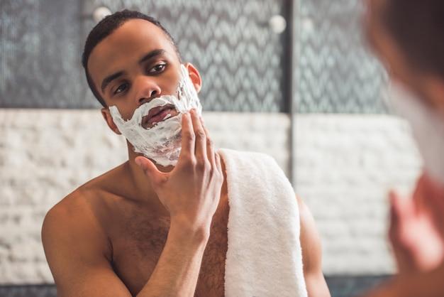 De mens past scheerschuim toe terwijl hij in de spiegel onderzoekt.