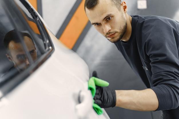 De mens poetst een auto in een garage op