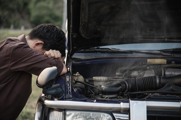 De mens probeert een motor van een motorprobleem op een lokale weg te bevestigen