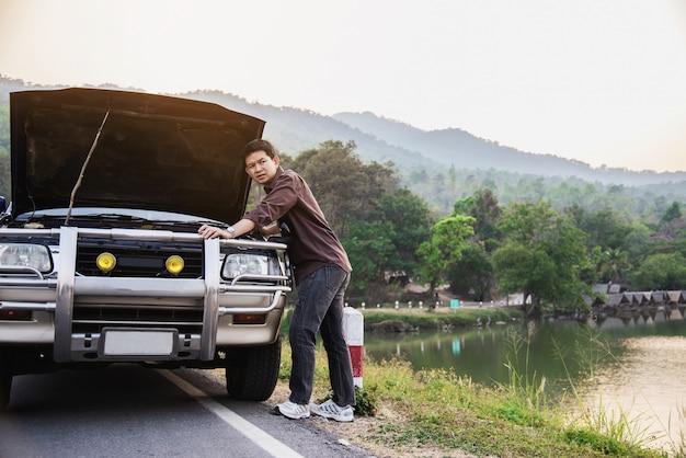 De mens probeert om een motor van een autoprobleem op een lokale weg chiang mai thailand te bevestigen