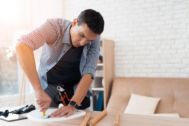 De mens probeert zijn koffietafel en krukken te vouwen.