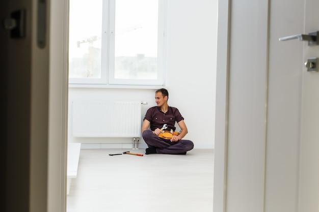 De mens repareert de radiatorbatterij in de kamer. onderhoud reparatie werkt renovatie in de flat. restauratie verwarming. moersleutel in handen