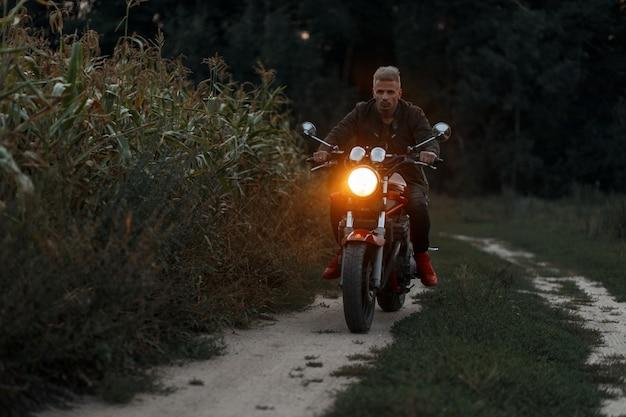 De mens rijdt 's avonds op een motorfiets met licht in een korenveld