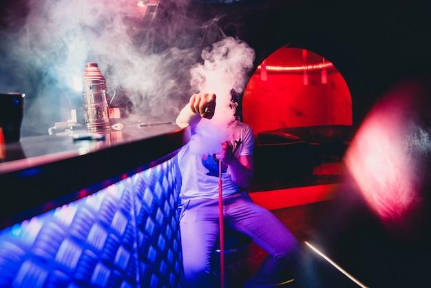 De mens rookt een waterpijp en ademt een grote wolk tabaksrook in